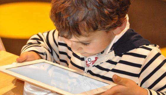 Enfant connecte avec une tablette à Internet